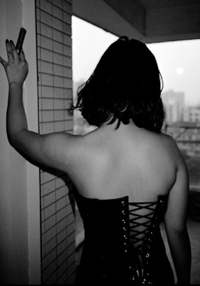 mistress wu wearing a black leather corset and standing on the balcony at 1106 west guangfu road